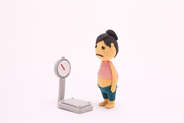 体重計を見つめる