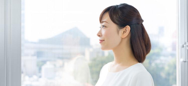 窓から外を見る女性の写真